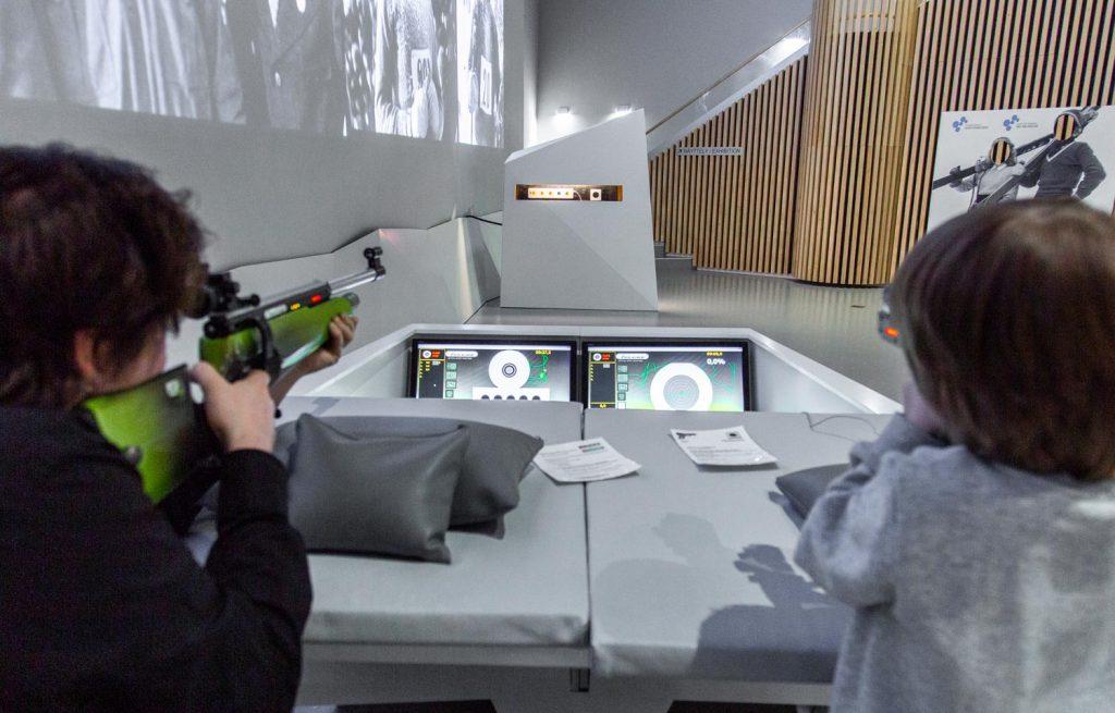 Kaksi lasta tähtää ampumahiihdon laseraseilla kohti maalitauluja.