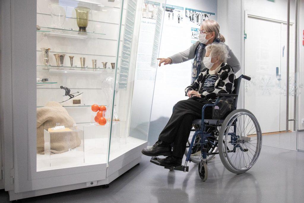 Nainen pyörätuolissa katselee palkintovitriiniä.